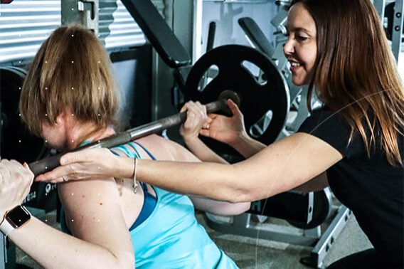 personal trainer helping female client with squat with weight