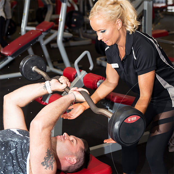 fitness trainer help male client with bench press. blog article how to build trust
