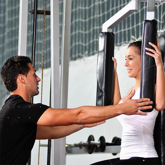 need a fitness trainer image personal trainer with client on arm press machine.