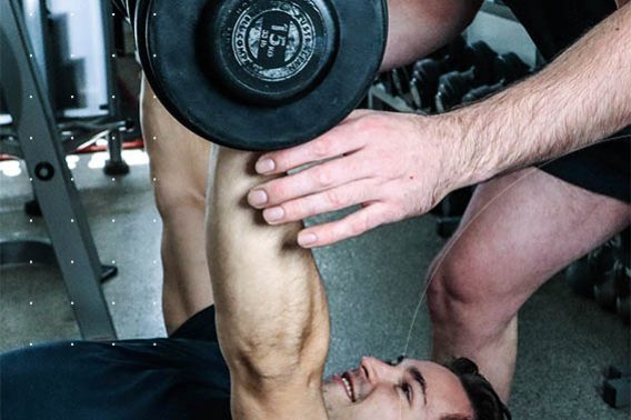 man doing dumbbell press. Blog article Are you over training?