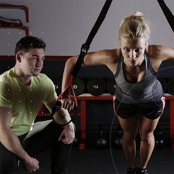 professional fitness trainer with client on TRX machine